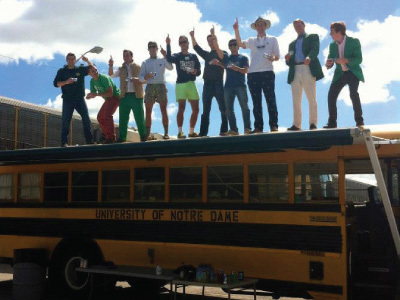 Students hold up number 1 while on top of bus